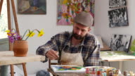 4К Young artist sitting and painting in workshop video
