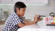Young Asian Boy Playing Game On Mobile Device Shot On R3D video