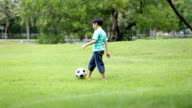 Young asian boy playing soccer in a park video