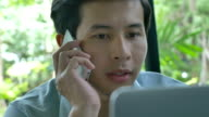 4K : Young Asian businessman using a laptop while talking on mobile video