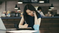 Young Asian Businesswoman Taking Order by Phone and Laptop video