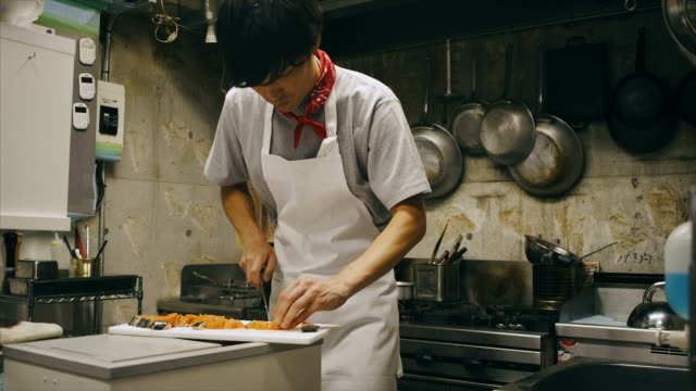 Young Asian Chef in Kitchen Cutting Salmon video