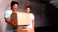 Young asian couple unpacking moving boxes video