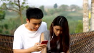 young asian couple using smart phone smiling video