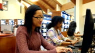 Young Asian female college student works on assignment at desktop computer in library video