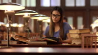 DS Young Asian female student studying in library video