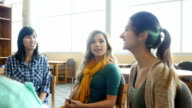 Young Asian female teacher leads a study or support group in library at STEM school video