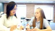 Young Asian female teacher teaching junior high school student about atoms video