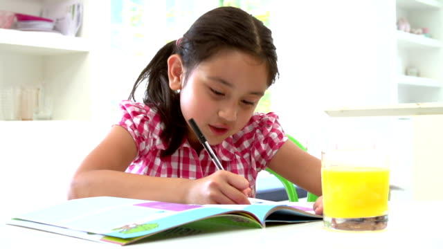 Young Asian Girl Doing Homework Seated At Table video
