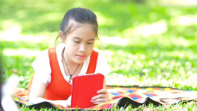 Young asian girl using tablet on the park video