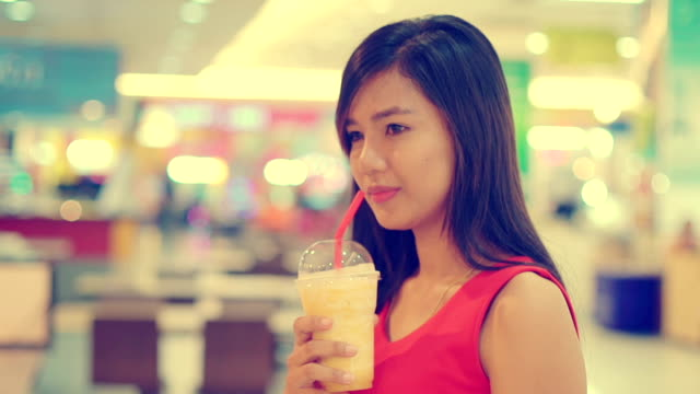 Young Asian Lady drinking fruit shake in mall toned video video