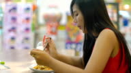 Young Asian Lady eating in mall food court video