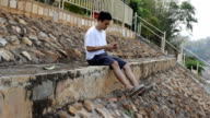 young asian man listening music outdoor video