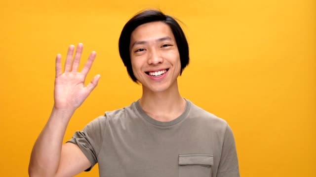 Young asian man smiling and waving to friends looking at camera isolated over yellow background. video