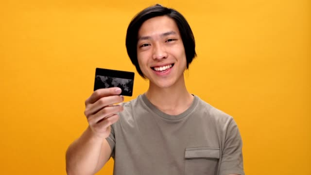 Young asian man smiling showing okay gesture and credit card isolated over yellow background. video
