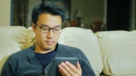 A young Asian man with glasses. He is sitting on the couch at home, reading e-book video