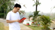 young asian man with tablet computer standing in park video