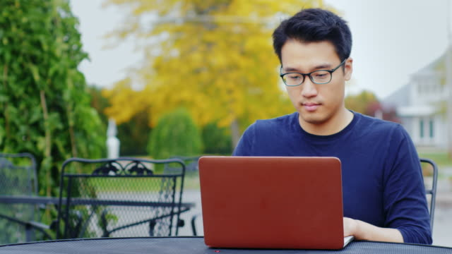 A young Asian man works with a laptop. Sitting outdoors in a typical American town video