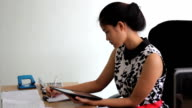 Young Asian Office Worker Using Her Tablet At Work video