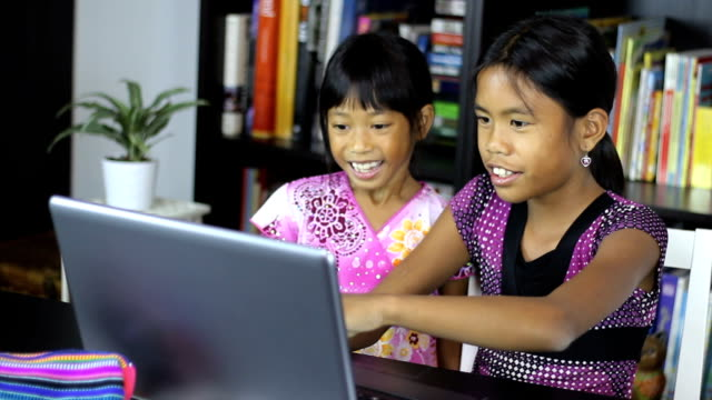 Young Asian Sisters Having Fun On Their Computer video