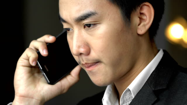 Young Asian Thai Businessman on the mobile phone working in cafe video