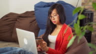 Young asian woman buy online on the computer sitting on the bean bag chair video