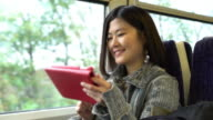Young Asian woman digital tablet on a train. video
