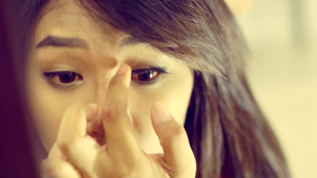 Young Asian Woman glues eyelashes. Toned video video