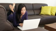 Young Asian Woman lying on couch with laptop video