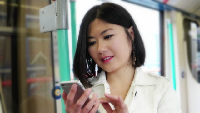 Young Asian woman on a train using her mobile phone. video