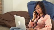 Young asian woman talking on the telephone sitting on the bean bag chair video