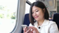 Young Asian woman text messaging on a train. video