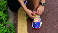 young asian woman tying shoelace on trail video