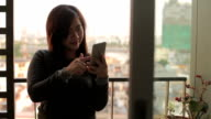 Young asian woman using mobile phone on sunset video