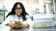 Young Asian women scientist play phone game in laboratory video