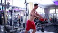 Young athletic man doing exercise in gym. Shallow depth of field. Biceps curls in gym machine standing. video