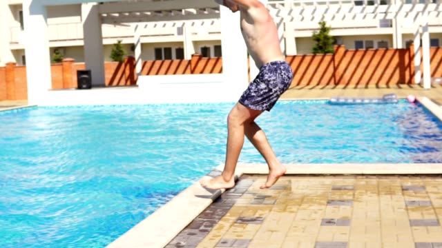 Young athletic man in swim shorts running and jumping spinning to the swimming pool. Slowmotion shot. video