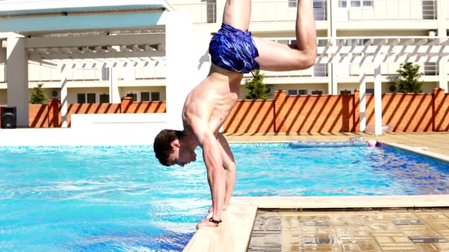 Young athletic man in swim shorts running and jumping to the swimming pool standing on his hands. Slowmotion shot. video