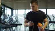 Young athletic man is listening to music on a smartphone while walking in sport gym with treadmills. video