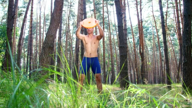 Young athletic man, with a bare, naked torso, performs strength exercises with heavy weight plate, element of gym. Slow motion. In pine forest, in summer, in rays of sun video