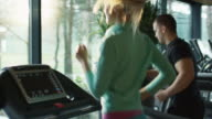 Young athletic men and women exercising and running on treadmill in sport gym. video