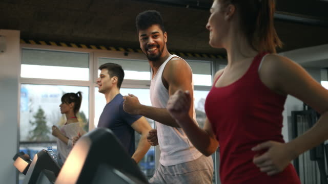 Young athletic people running on treadmills while exercising in a gym. video