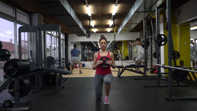 Young athletic woman exercising with weight disc in a gym. video