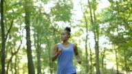 Young athletic woman running off road comes into view and rests, checking her watch video
