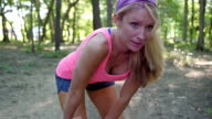 Young athletic woman stretching muscles before running in park video