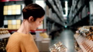 Young attractive brunette girl at the store chooses bright gold Christmas decor video