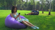 Young attractive brunette girl is sitting in a chair in the park and gaining a message on the phone video