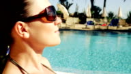 Young attractive brunette woman sunbathing by the pool video