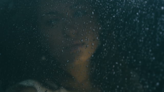 Young attractive Caucasian woman sitting in the car on a rainy day, drops fall on the window. video