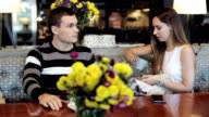 Young attractive couple chatting together at cafe video